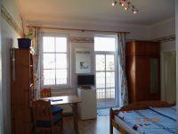 Das mit Laminat ausgelegte Doppelzimmer - mit angrenzendem Balkon - ist zweckmäßig eingerichtet, mit Doppelbett (bezogen mit Spezialbettwäsche), einer Sitzgruppe mit Tisch, Kleiderschrank, kleine Kommode und Bücherregal. Ferner sind TV mit DVD-Spieler und Radiowecker (mit CD) vorhanden. - Bild 3: Balkonzimmer *** / Pension Villa Erika * im Seebad Lubmin * Ostsee