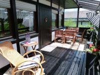 Die gemütliche Sitzecke und der Schaukelstuhl laden zum Relaxen und Verweilen ein. - Bild 3: Eifel-Ferienhaus Fliegenpilz - für Ihren Urlaub mit und ohne Hund
