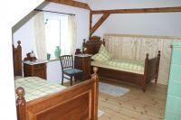 In diesem liebevoll eingerichteten Raum finden sich zwei einzelne Betten mit Nachttischchen. Die Wäsche kann in einer antiken Kommode verstaut werden. - Bild 9: Ferienhaus Beestland am Rande der Mecklenburgischen Schweiz für 6 Personen