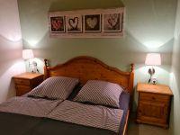 Schlafzimmer mit Doppelbett, zweitürigem Schrank, zwei Nachttischen und Garderobe. Zum Schlafzimmer gehört eine separate Toilette mit Waschbecken. - Bild 18: Ferienhaus Waldhäuschen Zandt- Bayerischer Wald