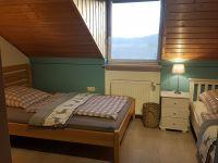 Schlafzimmer mit zwei Einzelbetten, Schrank und Tisch. Zum Schlafzimmer gehört eine separate Toilette mit Waschbecken. - Bild 21: Ferienhaus Waldhäuschen Zandt- Bayerischer Wald